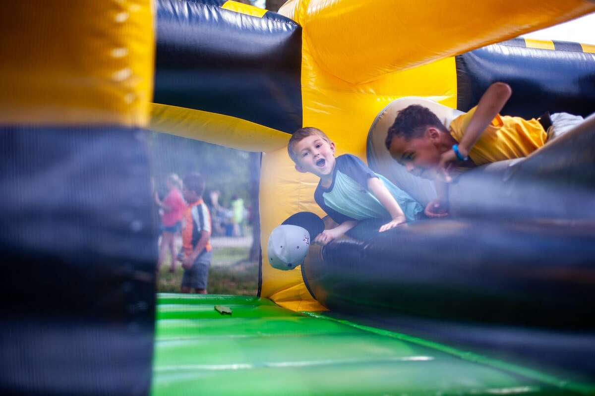 Kids crawl through an inflatable obstacle course at the Sanford Rising event on Saturday, May 22, 2021.