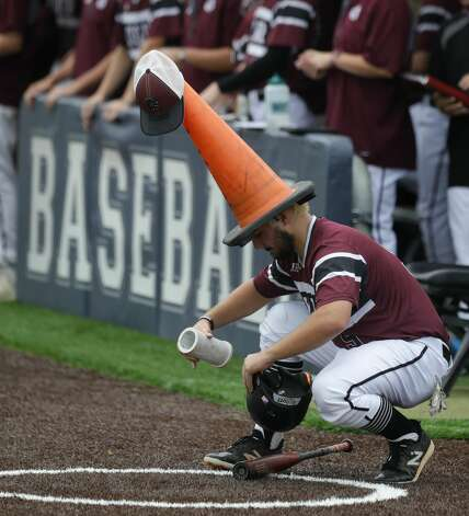 Will Herr #9 of Cy-Fair picks up batting equipment wearing a traffic cone on his hear between half innings during Game 3 of a Region II-6A high school baseball quarterfinal series at Tomball Memorial High School, Saturday, May 22, 2021, in Tomball. Photo: Jason Fochtman/Staff Photographer / 2021 © Houston Chronicle