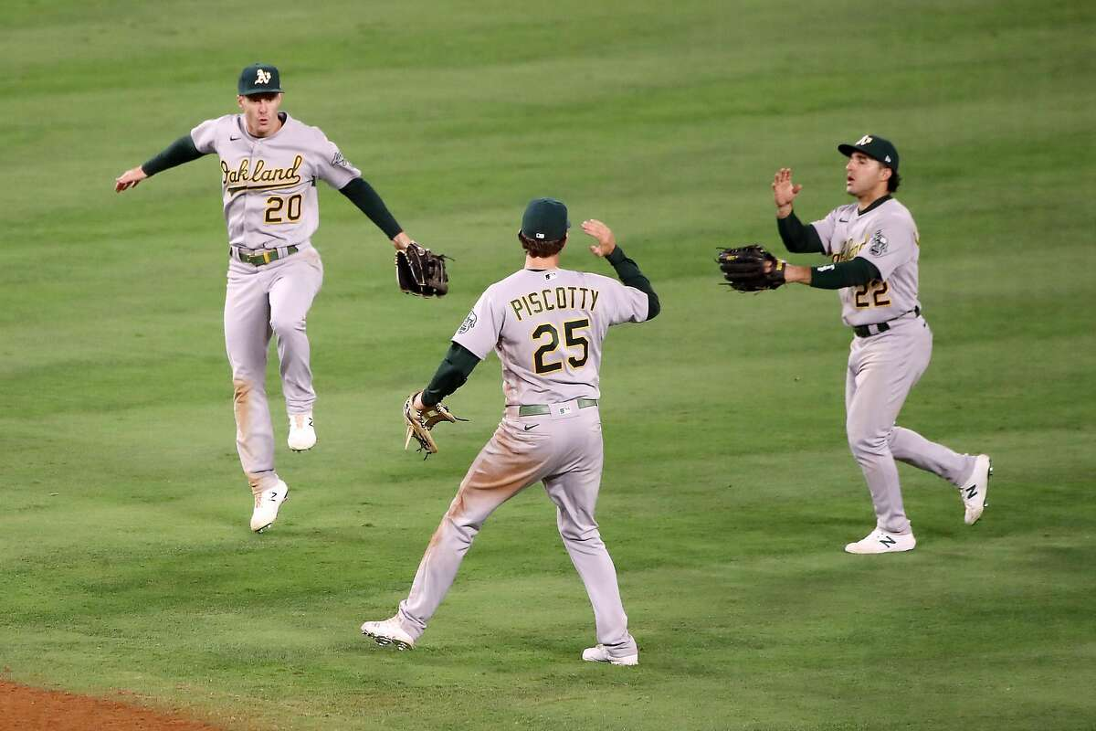 ANAHEIM, CALIFORNIA - MAY 21: Mark Canha #20, Stephen Piscotty #25 and Ramon Laureano #22 of the Oakland Athletics celebrate their 8-4 win against the Los Angeles Angels after the game at Angel Stadium of Anaheim on May 21, 2021 in Anaheim, California. (Photo by Katelyn Mulcahy/Getty Images)