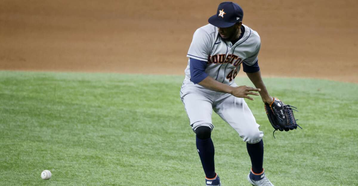Houston Astros relief pitcher Enoli Paredes (48) makes an error while trying to field a ball hit by Texas Rangers' Isiah Kiner-Falefa during the seventh inning of a baseball game Saturday, May 22, 2021, in Arlington, Texas. (AP Photo/Michael Ainsworth)