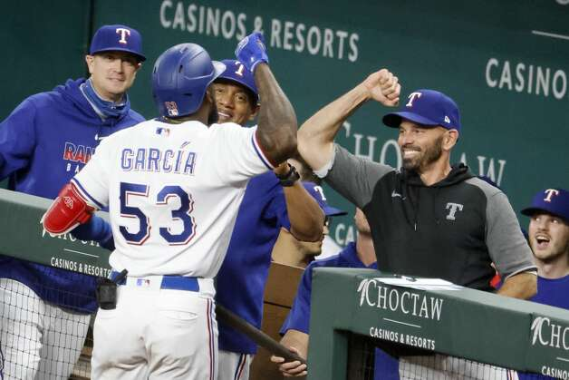 Texas Rangers' Adolis Garcia (53) celebrates his second solo home run with manager Chris Woodward, front right, during the seventh inning of a baseball game against the Houston Astros, Saturday, May 22, 2021, in Arlington, Texas. (AP Photo/Michael Ainsworth) Photo: Michael Ainsworth/Associated Press / Copyright 2021 The Associated Press. All rights reserved.