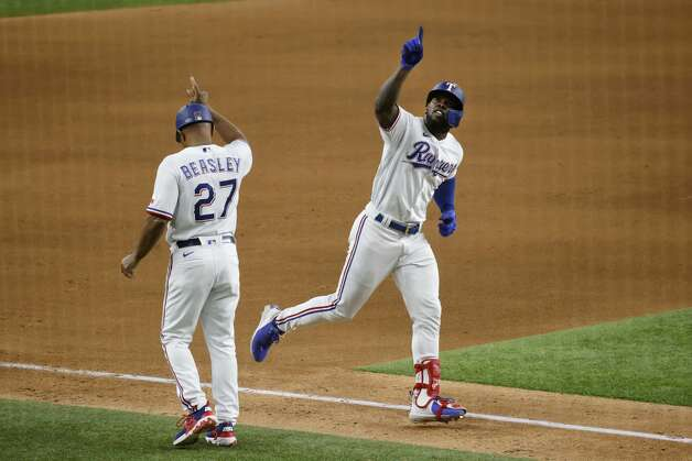 Texas Rangers' Adolis Garcia, right, celebrates his second solo home run with third base coach Tony Beasley (27) during the seventh inning of a baseball game against the Houston Astros, Saturday, May 22, 2021, in Arlington, Texas. (AP Photo/Michael Ainsworth) Photo: Michael Ainsworth/Associated Press / Copyright 2021 The Associated Press. All rights reserved.