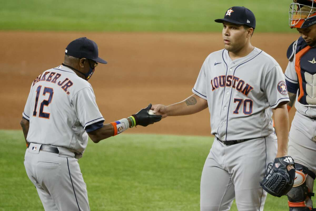 Houston Astros manager Dusty Baker Jr. (12) takes the ball from relief pitcher Andre Scrubb (70) as Scrubb is pulled from baseball game against the Texas Rangers during the seventh inning Saturday, May 22, 2021, in Arlington, Texas. (AP Photo/Michael Ainsworth)