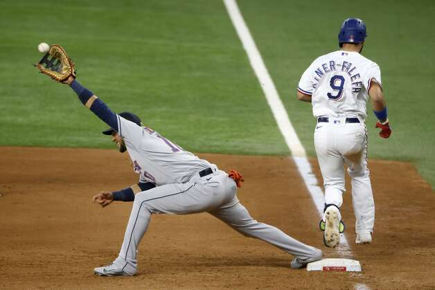 Houston Astros first baseman Yuli Gurriel (10) stretches for the ball as Texas Rangers' Isiah Kiner-Falefa (9) gets a single during the fifth inning of a baseball game Saturday, May 22, 2021, in Arlington, Texas. (AP Photo/Michael Ainsworth) Photo: Michael Ainsworth/Associated Press / Copyright 2021 The Associated Press. All rights reserved.