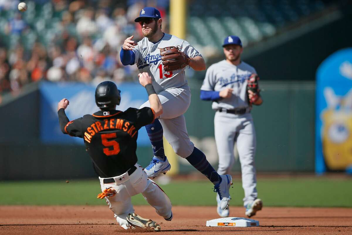The Los Angeles Dodgers second baseman Max Muncy (13) forces out San Francisco Giants Mike Yastrzemski (5) and throws to first to force out the Giants' Buster Posey (28) at first base for the double play in the first inning during an MLB game at Oracle Park, Saturday, May 22, 2021, in San Francisco, Calif.