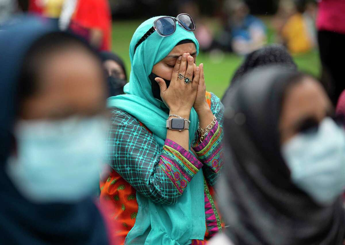 Participants in a Houston Stands with Palestine rally pray at Gerald D. Hines Waterwall Park after a march around the Galleria area Saturday. The rally occurred on the same day as the first full day of a cease-fire between Israel and Hamas.