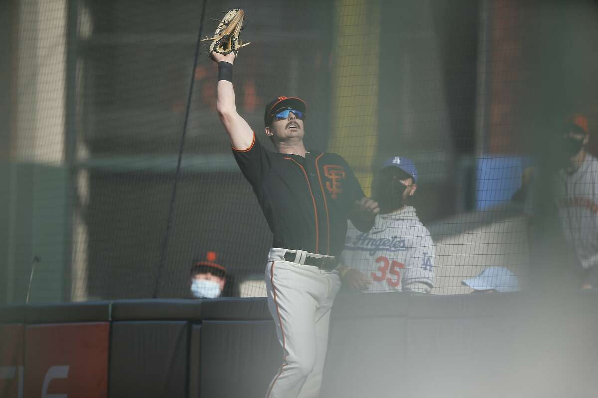San Francisco Giants right fielder Mike Yastrzemski (5) makes the out in foul territory on a fly ball by Los Angeles Dodgers starting pitcher Walker Buehler (21) in the fifth inning during an MLB game at Oracle Park, Saturday, May 22, 2021, in San Francisco, Calif.