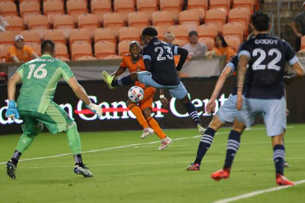 Houston Dynamo FC midfielder Fafa Picault (10) shoots between the legs of Vancouver Whitecaps FC defender Javain Brown (23) during the first half of an MLS match Saturday, May 22, 2021, at BBVA Stadium in Houston. Photo: Jon Shapley/Staff Photographer / © 2021 Houston Chronicle
