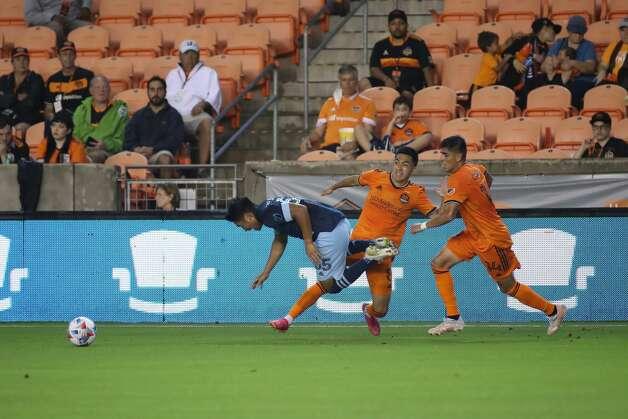 Houston Dynamo FC midfielder Memo Rodriguez (8) tackles Vancouver Whitecaps FC midfielder Michael Baldisimo (55) during the second half of an MLS match Saturday, May 22, 2021, at BBVA Stadium in Houston. Photo: Jon Shapley/Staff Photographer / © 2021 Houston Chronicle