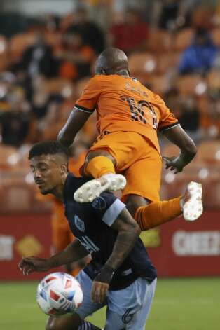 Houston Dynamo FC midfielder Fafa Picault (10) and Vancouver Whitecaps FC defender Bruno Gaspar (6) battle for control of the ball during the first half of an MLS match Saturday, May 22, 2021, at BBVA Stadium in Houston. Photo: Jon Shapley/Staff Photographer / © 2021 Houston Chronicle