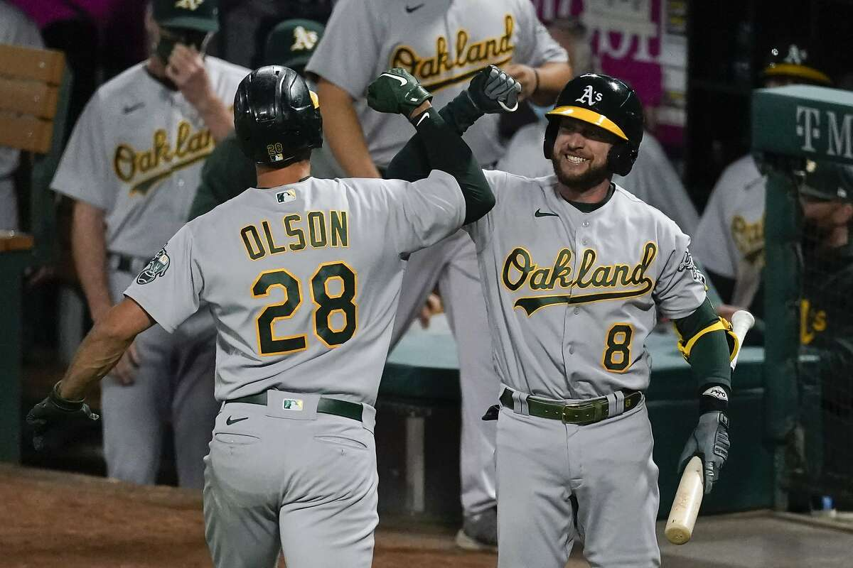 Oakland Athletics' Matt Olson (28) celebrates with Jed Lowrie (8) after hitting a home run during the sixth inning of a baseball game against the Los Angeles Angels Saturday, May 22, 2021, in Anaheim, Calif. (AP Photo/Ashley Landis)