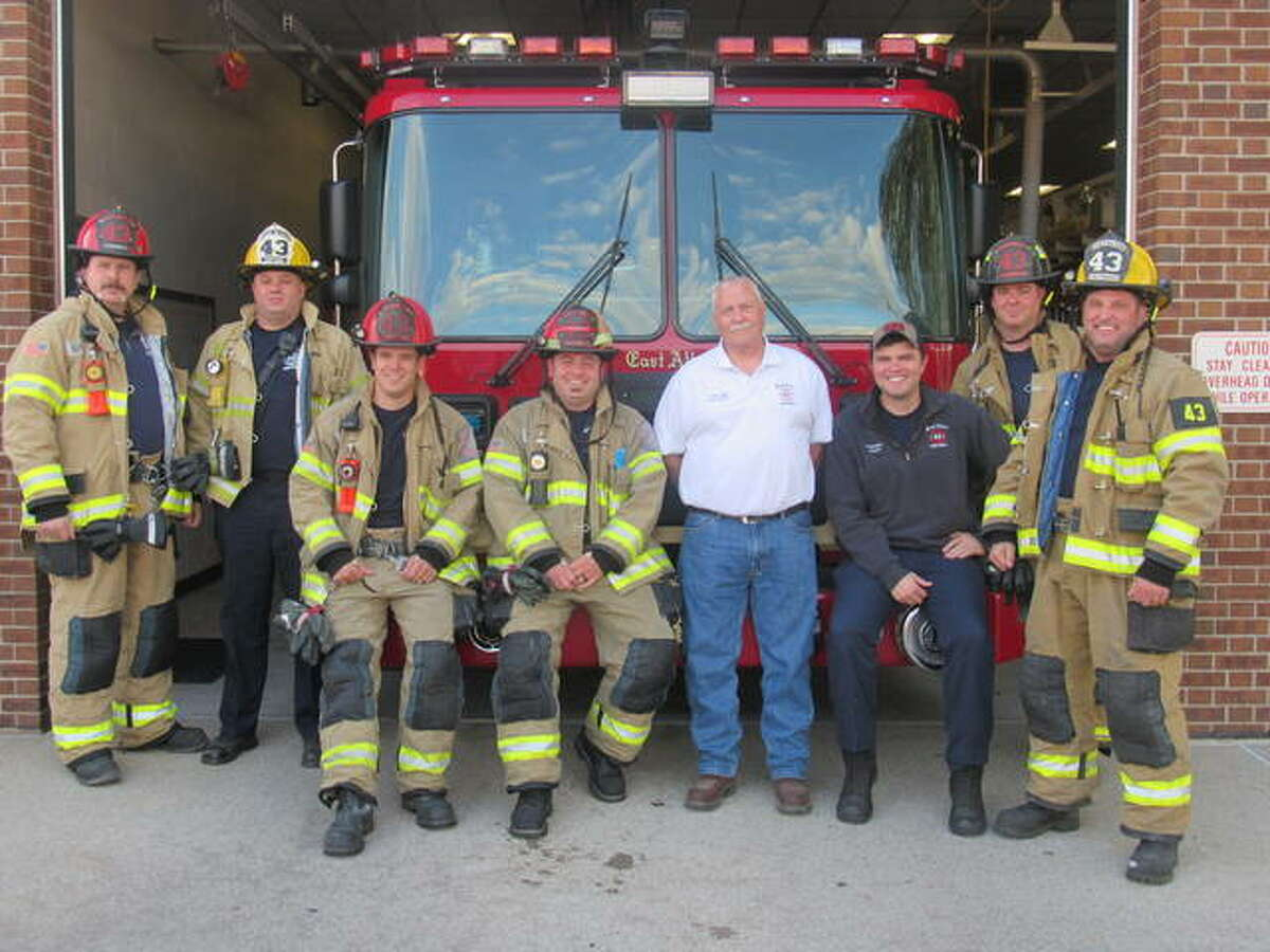 East Alton Fire Chief Tim Quigley, center, is surrounded by members of the East Alton Fire Department: from left, Capt. Travis Burdick, Capt. Jed Downs, Eng. Jeremy Diveley, Eng. Drew Mortland, Eng. Craig Kinder, Firefighter Nathan Friedrich and Lt. Eric Ruden. The department will mark its 100th year this week.