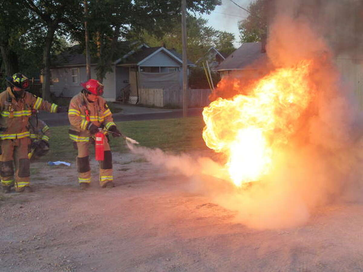 East Alton firefighters practice putting out a fire with an extingisher. The department will mark its 100th anniversary this week.