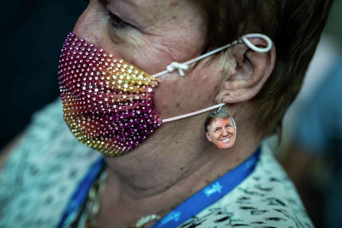 A woman wearing earrings featuring former president Donald Trump watches as Sen. Tom Cotton, R-Ark., speaks during an interview at the Conservative Political Action Conference on Feb. 26 in Orlando.