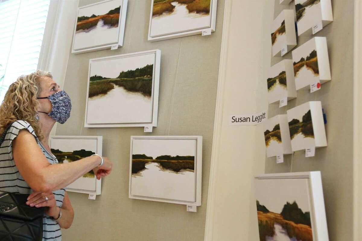 Cathy Diamond of Westport enjoys the work of Susan Leggitt of Norwalk at the Westport Woman's Club's annual art show on Saturday, May 22, 2021.