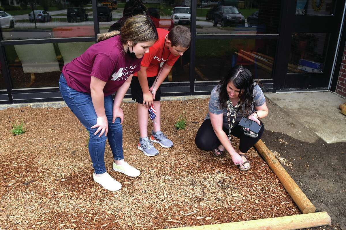 Sixth-graders Reese Lierhr (left) and Ross Curfman listen to Agriculture Club sponsor Ashley Scranton as she talks about a plant in the garden in front of the school.