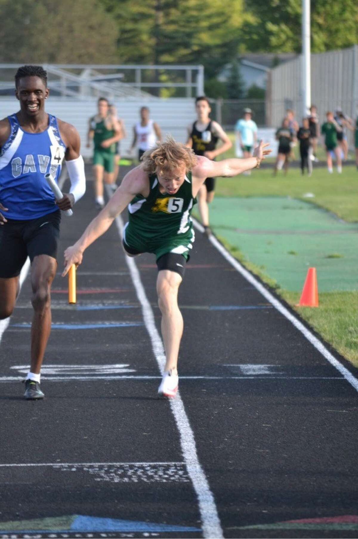 Dow High's Noah Reuter-Gushow edges out a runner from Flint Carman-Ainsworth to propel the Chargers' 1600-meter relay team to a regional championship during Saturday's Division 1 regional meet at Saginaw Heritage.