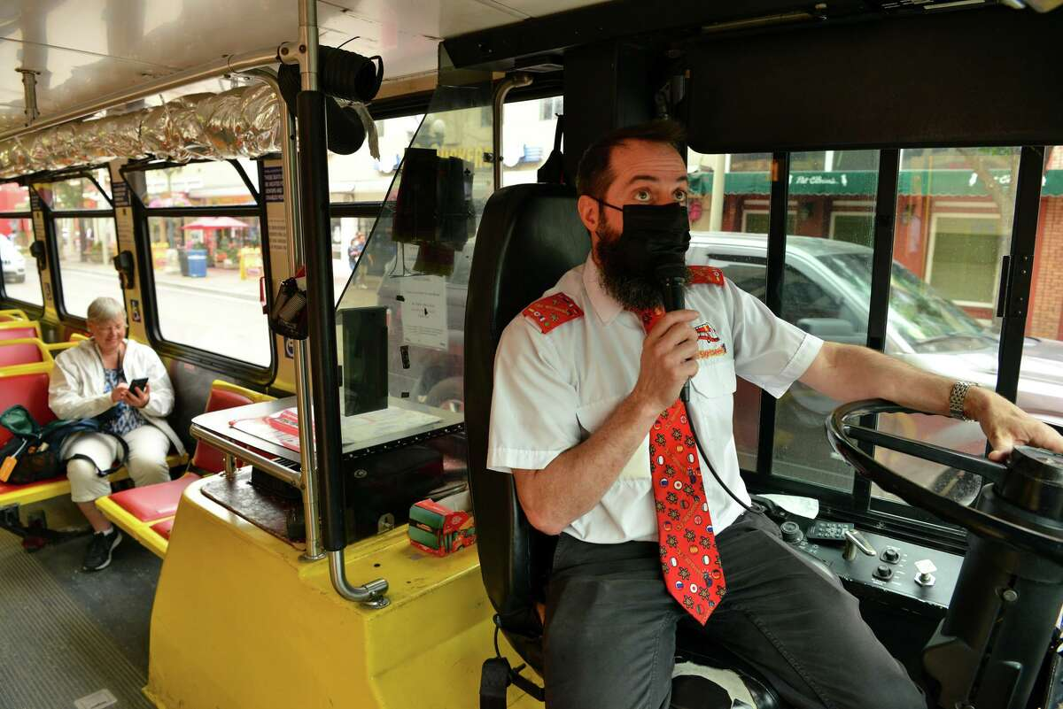 City Sightseeing driver Nick Stincelli briefs his passengers near the Alamo. The company is facing a lack of drivers and ticket hawkers.