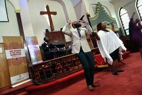 """From left, Kentrell Ragin on the organ and vocalists Jordan Watson, Marissa Murphy and Erica Wilkins Shirley """"Cookie"""" Frasier sing in prayer at the first in-person service since the COVID-19 pandemic began at Varick Memorial AME Zion Church in New Haven on May 23, 2021."""