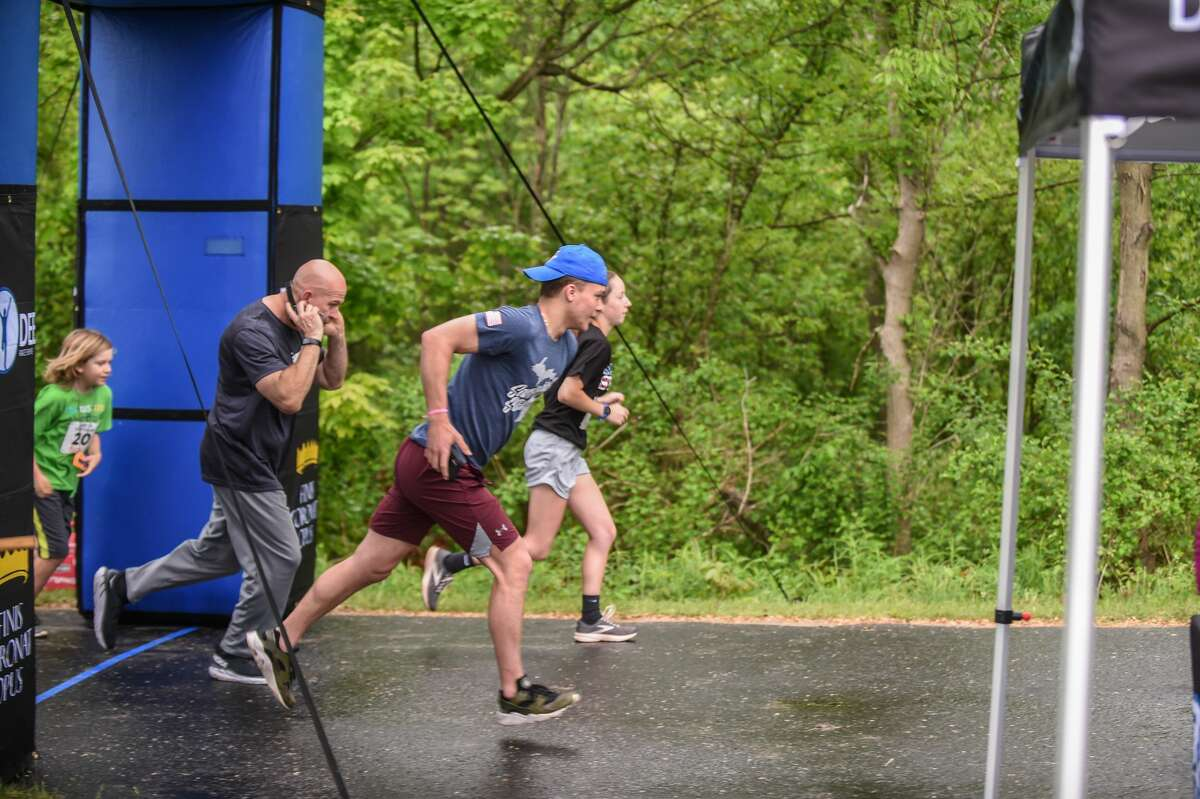 Dylan Glinski, center, takes off with other runners in the Smitty's 5K for the Four Lakes during Sanford Rising Saturday, May 22, 2021 in Sanford. (Adam Ferman/for the Daily News)