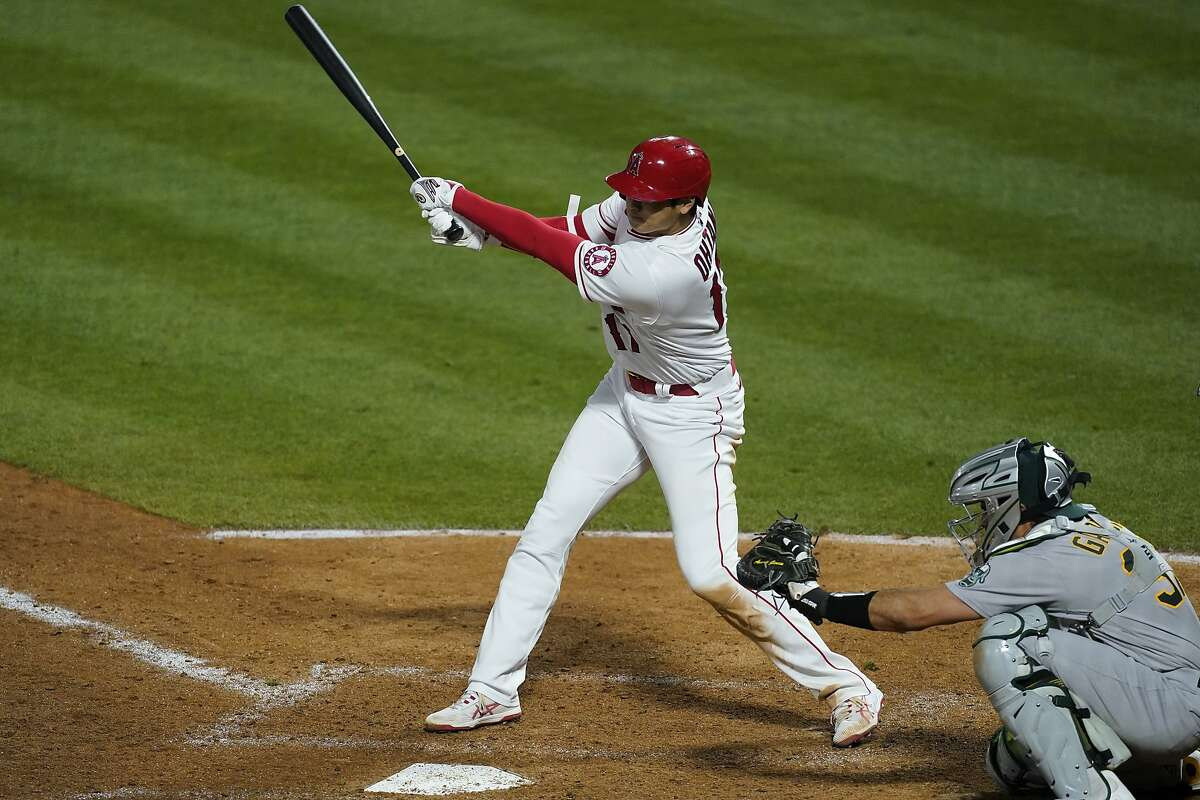 Los Angeles Angels designated hitter Shohei Ohtani (17) triples during the eighth inning of a baseball game against the Oakland Athletics Saturday, May 22, 2021, in Anaheim, Calif. Jose Iglesias scored. (AP Photo/Ashley Landis)
