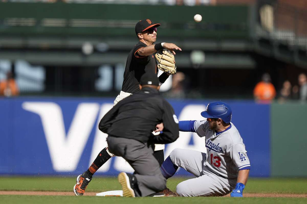 San Francisco Giants second baseman Mauricio Dubon, top, throws to first base for a double play after forcing out Los Angeles Dodgers' Max Muncy (13) during the fourth inning of a baseball game Saturday, May 22, 2021, in San Francisco. Dodgers' Albert Pujols was out at first base. (AP Photo/Tony Avelar)
