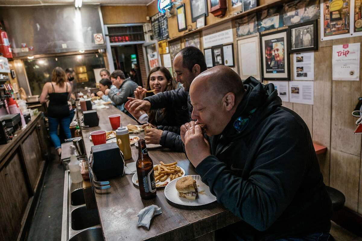 Michael Schaff, visiting from Mandan, N.D., eats a burger at Sam's in San Francisco, which is expected to receive Legacy Business Registry status this week.