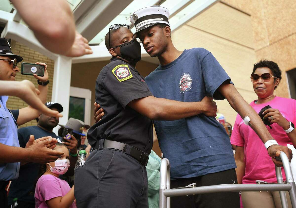 New Haven Firefighter Derrick Akel, left, hugs his firefighting partner, Lt. Samod