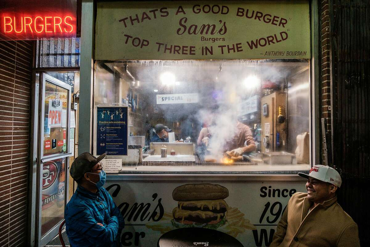Barry Duong and Richard Aspillera wait for their food outside Sam's Burgers in San Francisco.