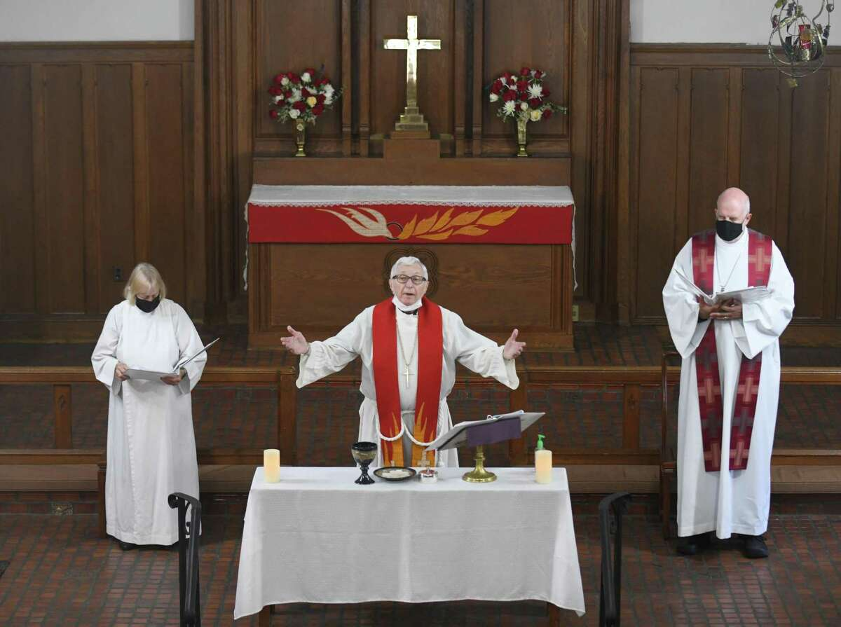 Lois Coffin, left, the Rev. Dr. Harvey Weitel, center, and Bishop Hazel Wood welcome congregants to the final church service at Zion Evangelical Lutheran Church in Stamford, Conn. Sunday, May 23, 2021.