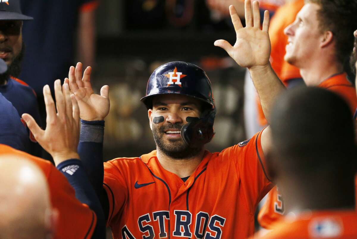 Houston Astros' Jose Altuve is greeted in the dugout by teammates after scoring against the Texas Rangers during the eighth inning of a baseball game in Arlington, Texas, Sunday, May 23, 2021. (AP Photo/Ray Carlin)