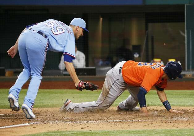 Houston Astros' Jason Castro, right, avoids a tag by Texas Rangers relief pitcher Brett de Geus, left, as he scores on a wild pitch during the eighth inning of a baseball game in Arlington, Texas, Sunday, May 23, 2021. (AP Photo/Ray Carlin) Photo: Ray Carlin/Associated Press / Copyright 2021 The Associated Press. All rights reserved.