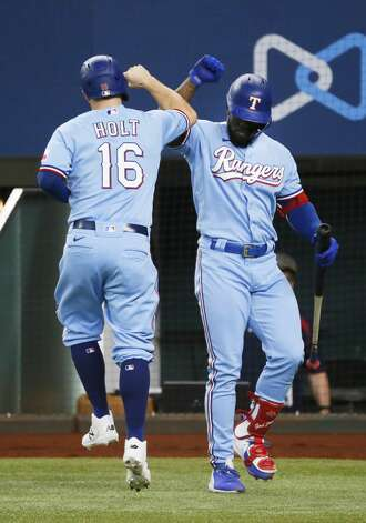 Texas Rangers' Brock Holt, left, is greeted at the plate by Adolis Garcia, right, after scoring on a base loaded walk against the Houston Astros during the fifth inning of a baseball game in Arlington, Texas, Sunday, May 23, 2021. (AP Photo/Ray Carlin) Photo: Ray Carlin/Associated Press / Copyright 2021 The Associated Press. All rights reserved.