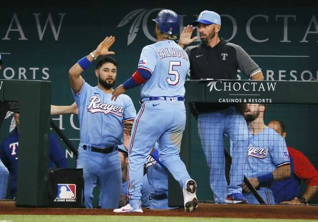 Texas Rangers' Willie Calhoun (5) is greeted at the dugout steps by Isiah Kiner-Falefa, left, and manager Chris Woodward, right, after scoring on a double by Nick Solak against the Houston Astros during the seventh inning of a baseball game in Arlington, Texas, Sunday, May 23, 2021. (AP Photo/Ray Carlin) Photo: Ray Carlin/Associated Press / Copyright 2021 The Associated Press. All rights reserved.