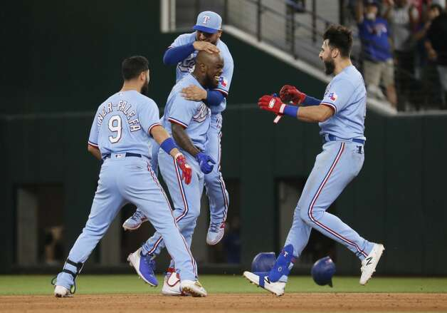 Texas Rangers' Adolis Garcia, bottom center, is hugged by Jose Trevino, top center, as Isiah Kiner-Falefa, left, and Joey Gallo, right, join in after a walk-off single against the Houston Astros in the tenth inning of a baseball game in Arlington, Texas, Sunday, May 23, 2021. (AP Photo/Ray Carlin) Photo: Ray Carlin/Associated Press / Copyright 2021 The Associated Press. All rights reserved.