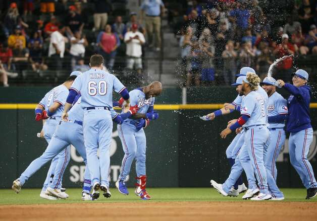 Texas Rangers' Adolis Garcia, center, is mobbed by teammates after a walkoff single against the Houston Astros in the tenth inning of a baseball game in Arlington, Texas, Sunday, May 23, 2021. (AP Photo/Ray Carlin) Photo: Ray Carlin/Associated Press / Copyright 2021 The Associated Press. All rights reserved.