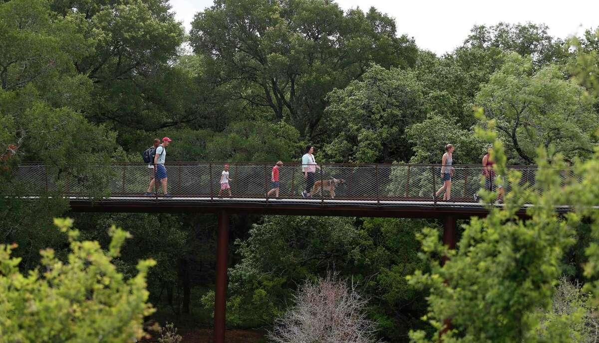 Visitors cross the Hardberger Park Sky Bridge on Sunday, May 23, 2021.