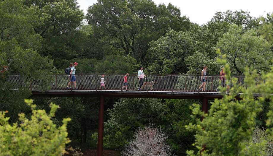 Visitors cross the Skywalk of the Robert L.B. Tobin Land Bridge at Phil Hardberger Park, which affords them a largely shaded view of the tree canopy. The $23 million land bridge is meant to help animals safely cross Wurzbach Parkway and to expand their natural habitat. Photo: Ronald Cortes /Contributor / / 2021 Ronald Cortes