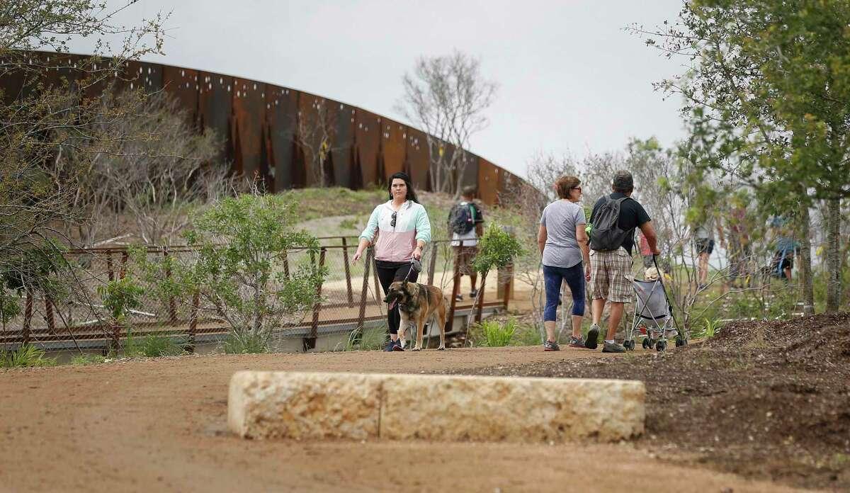 People walk along the Robert L.B. Tobin Land Bridge at Phil Hardberger Park.