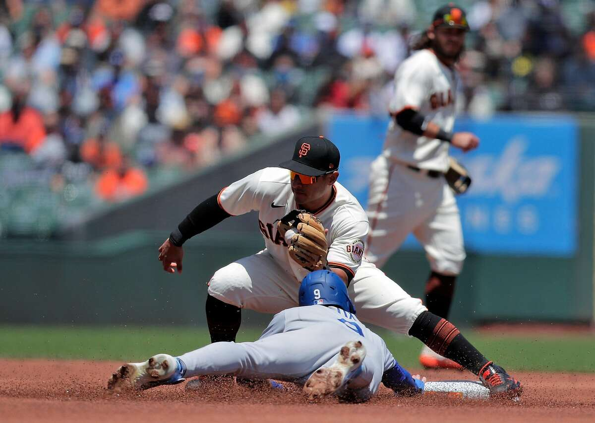 Donovan Solano (7) catches the throw from the catcher to get Gavin Lux (9) stealing in the first inning as the San Francisco Giants played the Los Angeles Dodgers at Oracle Park in San Francisco, Calif., on Sunday, May 23, 2021.