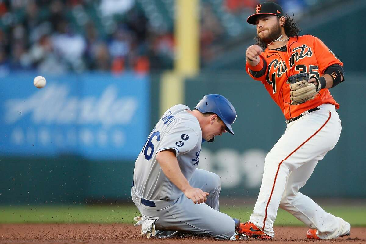 Giants shortstop Brandon Crawford (35) forces out Los Angeles Dodgers catcher Will Smith (16) at second base as he throws to first base in the second inning during an MLB game at Oracle Park, Friday, May 21, 2021, in San Francisco, Calif. Crawford's throw was not in time and Los Angeles Dodgers second baseman Gavin Lux (9) is safe at first base.