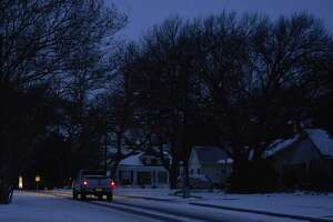 A truck drives down the street during a power outage in McKinney, Texas, on Feb. 16, 2021.