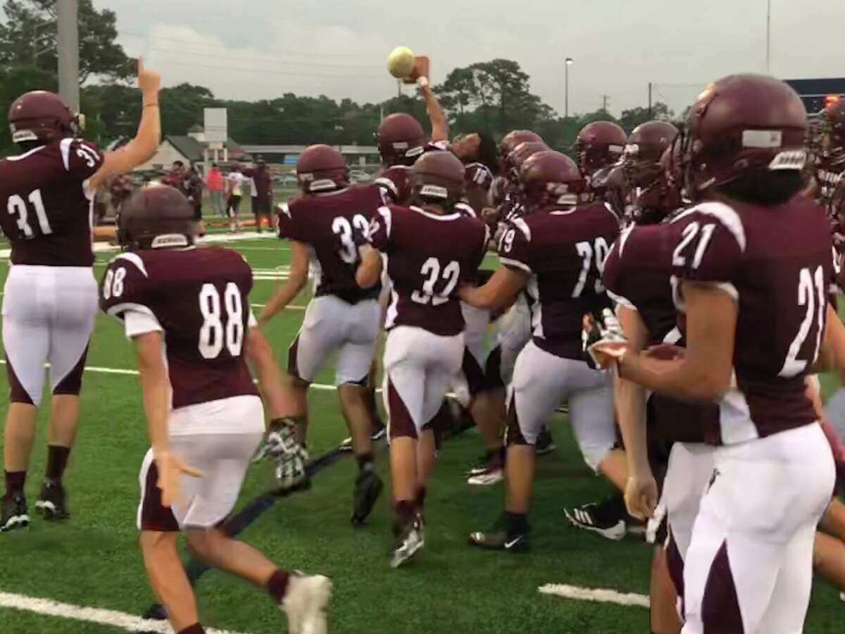 The maroon team grabs the Spring Game trophy and runs on the field after winning Northbrook's Spring Game on May 19 at Spring Woods High School