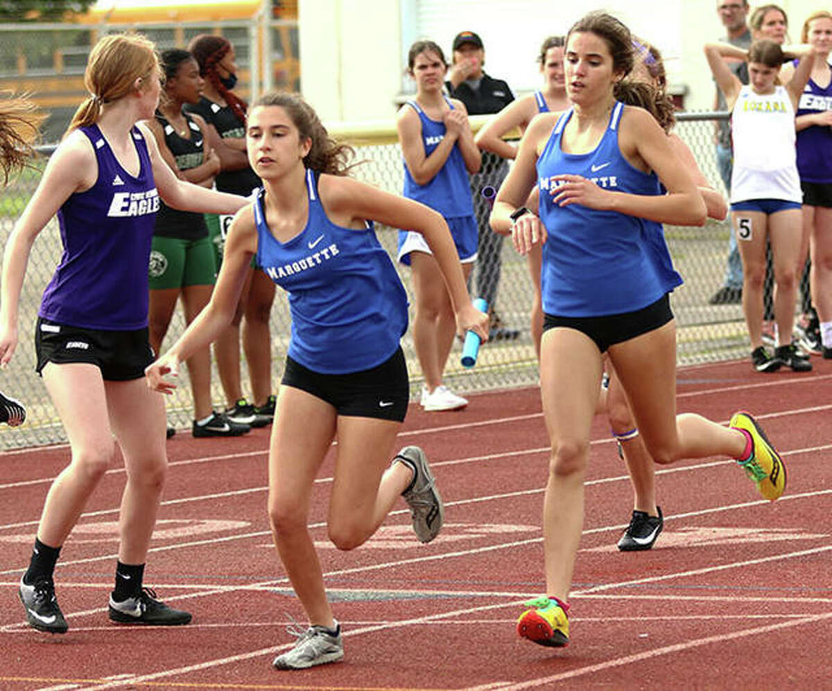 Marquette Catholic's Katie Johnson (second left) takes the baton from Kailey Vickrey (right) for the second leg of the 4x400 relay last week at the Madison County Small-Schools girls track meet at Memorial Stadium in Wood River.