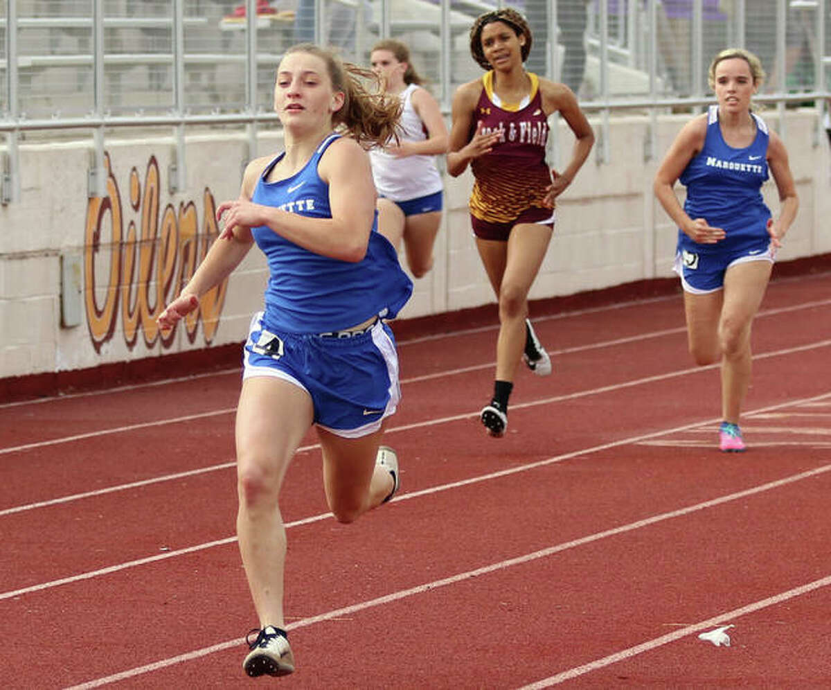 Marquette's Sammy Hentrich (left) approaches the finish in her victory in the 200 meters at the Madison County Small-Schools meet May 17 in Wood River.