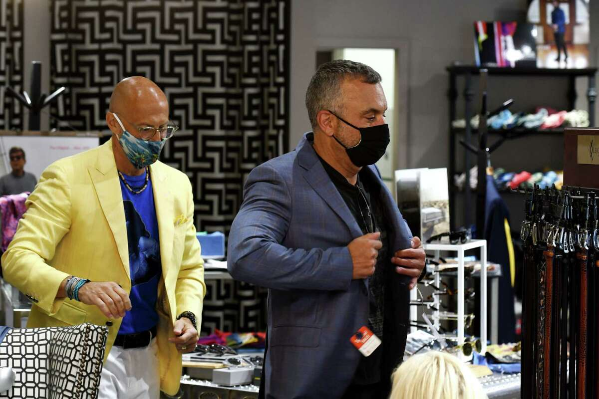 Robert Amore, proprietor of Amore Clothing, left, fits a new suit for customer, David Doerrer, at his Newton Plaza store on Friday, May 21, 2021, in Colonie, N.Y. (Will Waldron/Times Union)