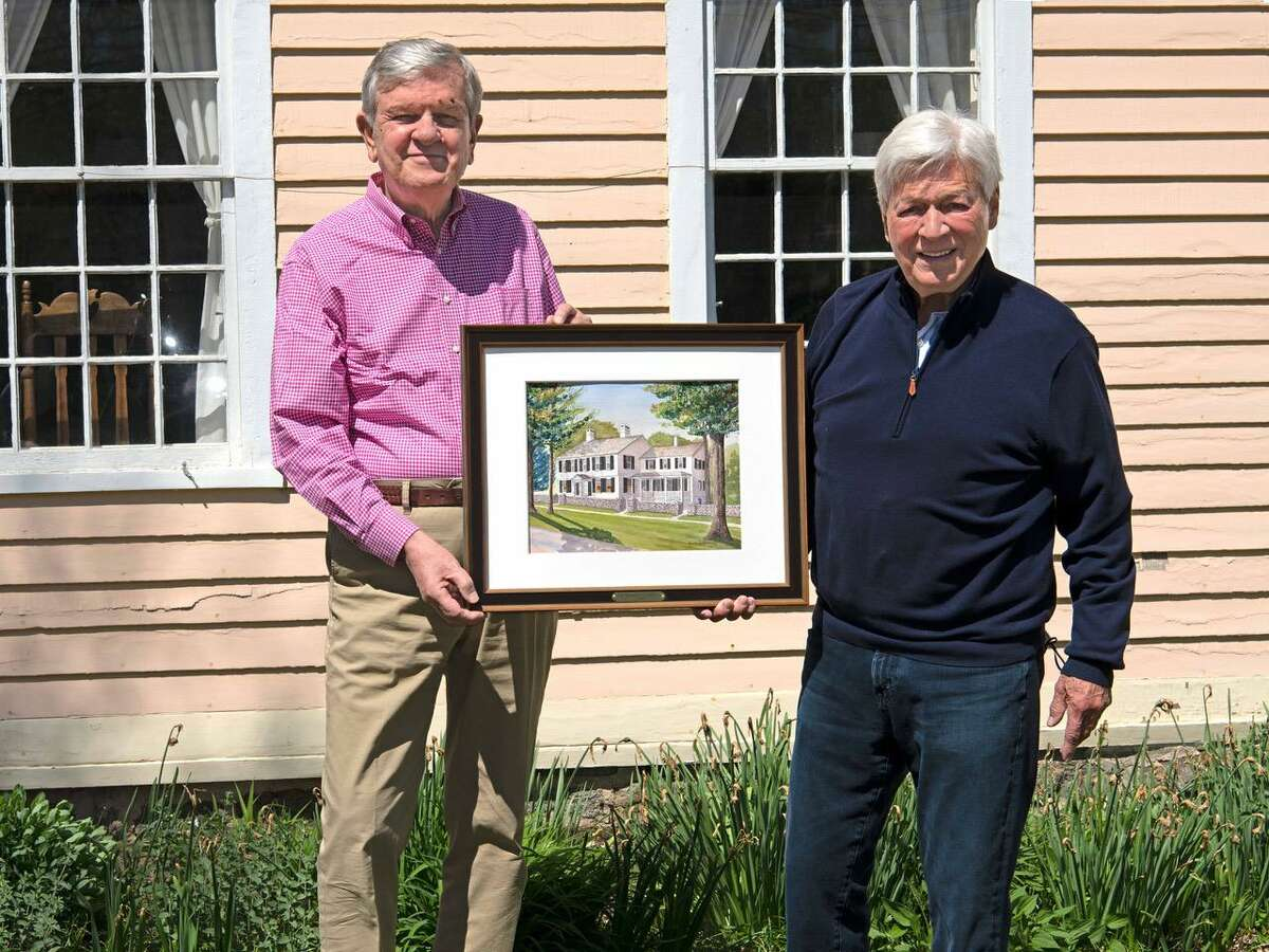 Artist Bill Dowling, right, offers his painting to Madison Historical Society President Mark Edmiston.