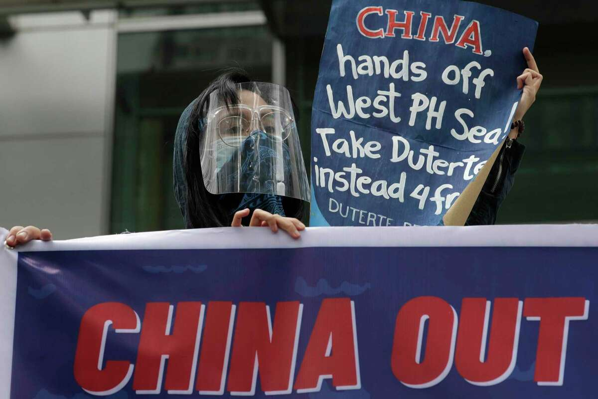 Protesters hold slogans during a rally outside the Chinese consulate in Metro Manila, Philippines on Friday, May 7, 2021. The group is demanding China to get out of Philippine-claimed territory in the South China Sea. (AP Photo/Aaron Favila)