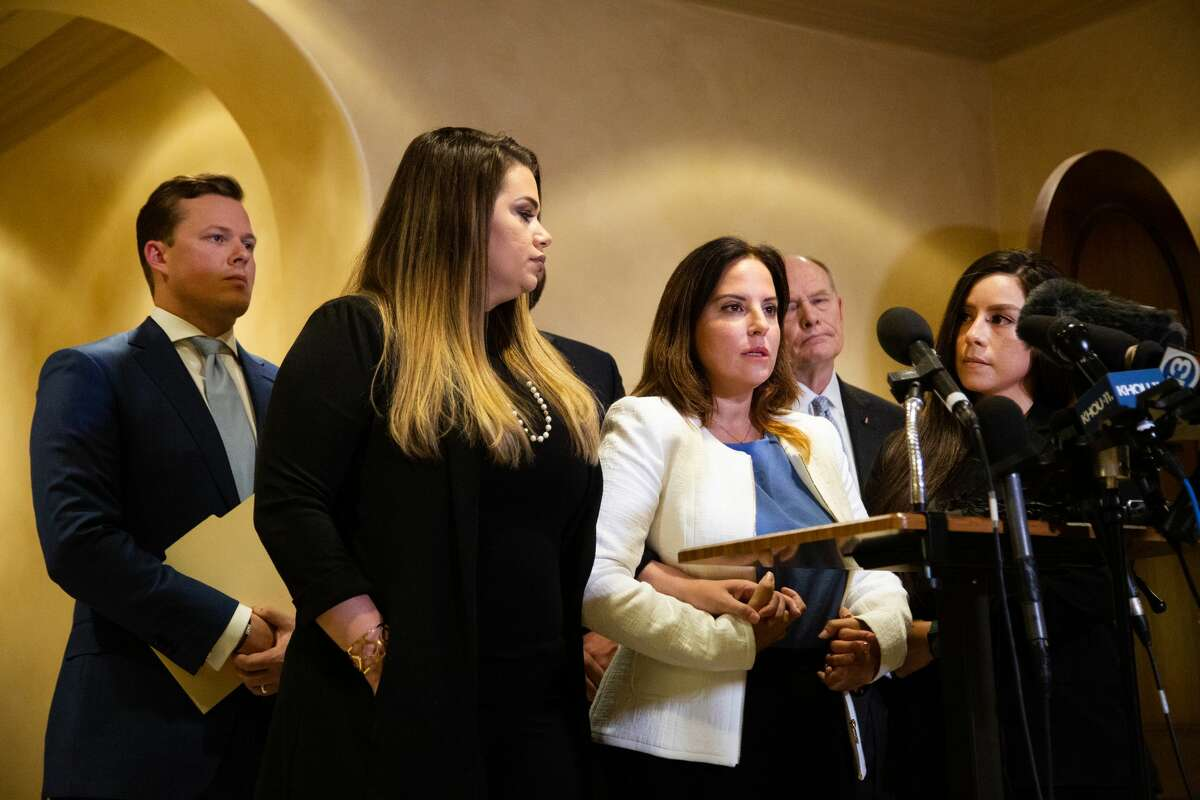 Jacquelyn Aluotto, center, talks to members of the press about alleged sexual misconduct against female deputies, Monday, May 24, 2021, in Houston.
