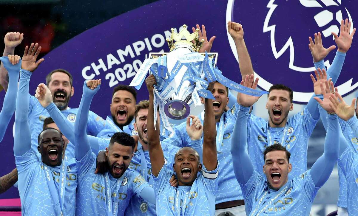 Manchester City's Fernandinho raises the trophy to celebrate winning the English Premier League title after the soccer match between Manchester City and Everton at the Etihad stadium in Manchester, Sunday, May 23, 2021.(Peter Powel/Pool via AP)